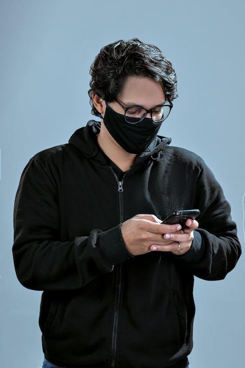 Man in Black Zip Up Jacket Holding Black Smartphone