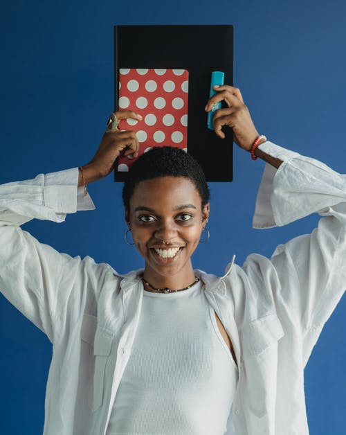 Cheerful smiling African American female student wearing casual clothes holding notebooks above head in studio and looking at camera happily