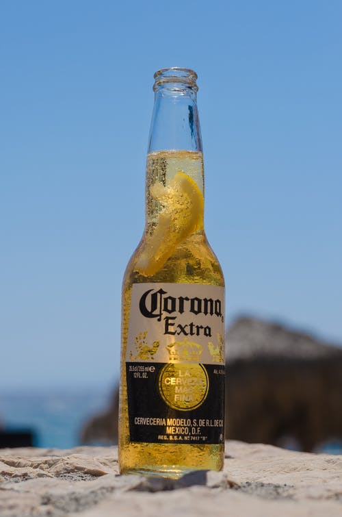 Corona Extra Beer Bottle on White Sand