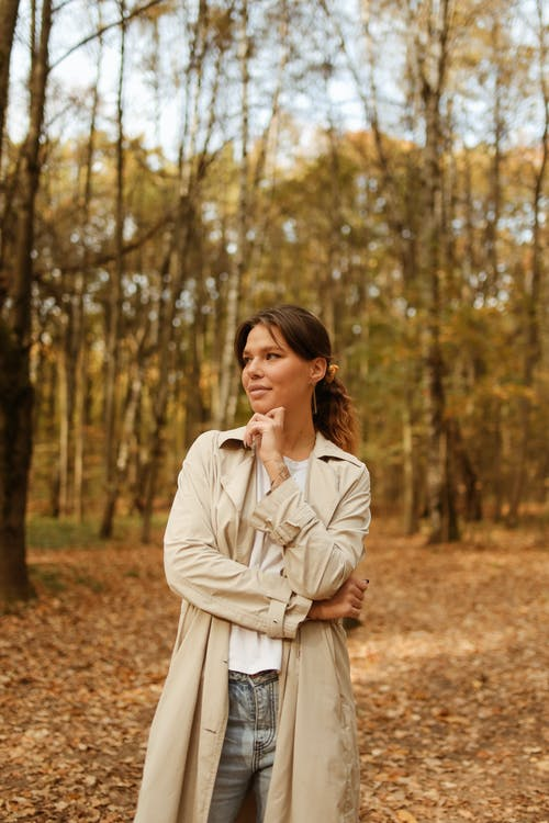 Woman in Beige Coat Standing on Brown Field Surrounded by Trees