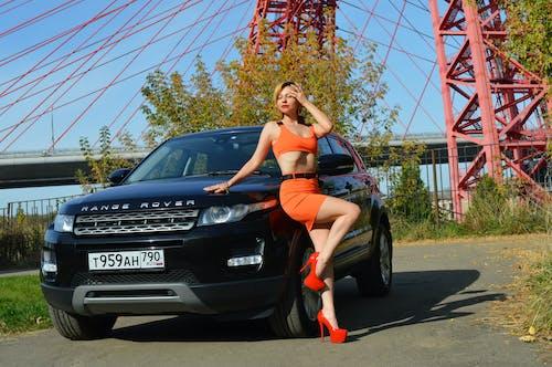 Trendy model near modern sports car on roadway