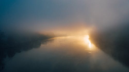 River illuminated by shiny light in foggy weather