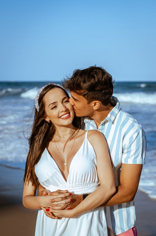 Happy couple embracing on sandy beach