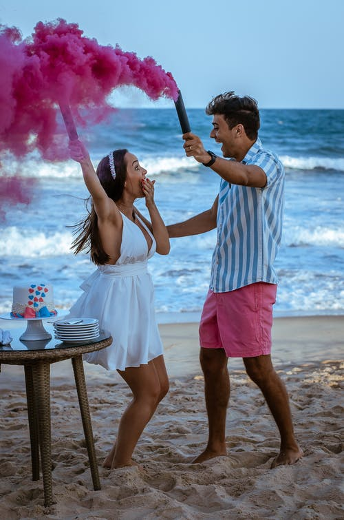 Full body side view of expressive couple with smoke bombs on sandy beach during gender party