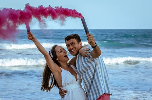 Cheerful pregnant couple in trendy apparels holding bomb of pink colorful smoke embracing near wavy ocean