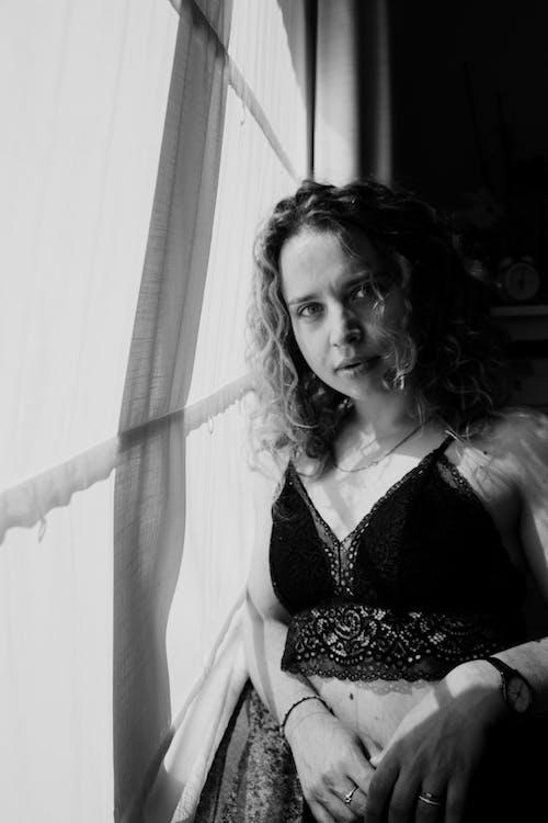 Sensual woman leaning on window curtain
