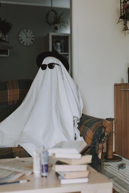 Person wrapped in white cloth pretending invisible