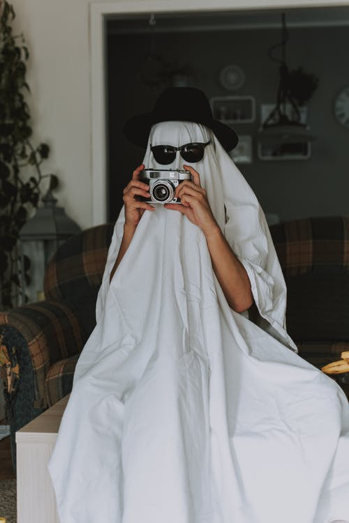 Person with old fashioned camera wrapped in white cloth