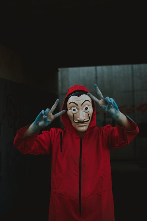 Person with dirty hands in mask and overall