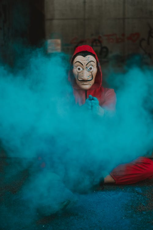 Person in scary mask and hood sitting on ground covered with color powder