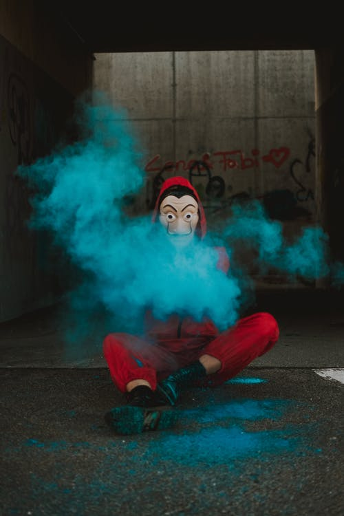 Person in frightening mask covered with bright powder