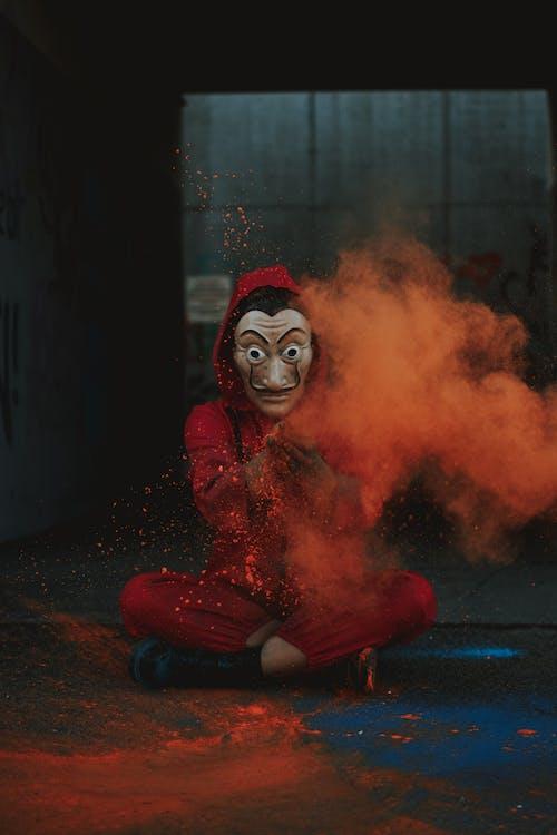Full body of artistic creative person in costume and Dali mask spreading orange powder on street