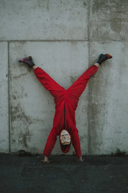 Full body of person in scary costume standing upside down leaning on concrete wall