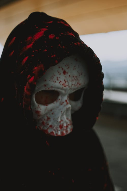 Person wearing scary mask and hood