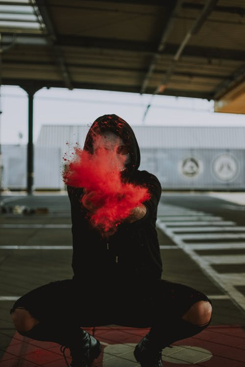 Man with face under mask in black outfit squatting while throwing powder around