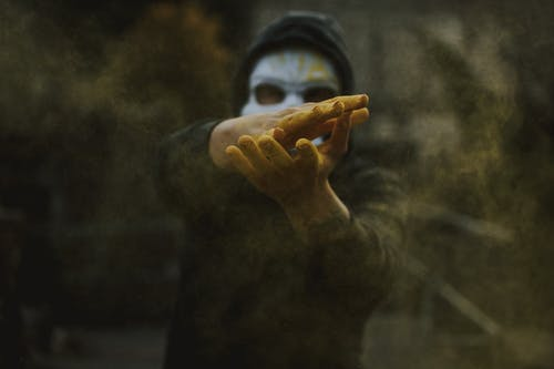 Man in mask clapping hands and spreading powder
