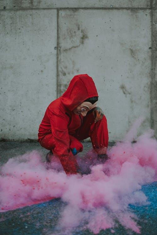 Person in red overall and mask in cloud of powder
