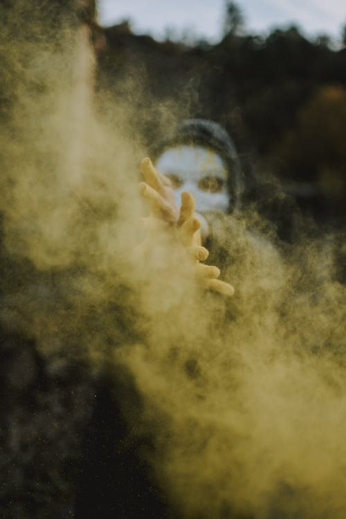 Man in scary mask spreading yellow powder