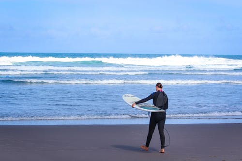 Man in Black Jacket Holding White Surfboard Walking on Beach