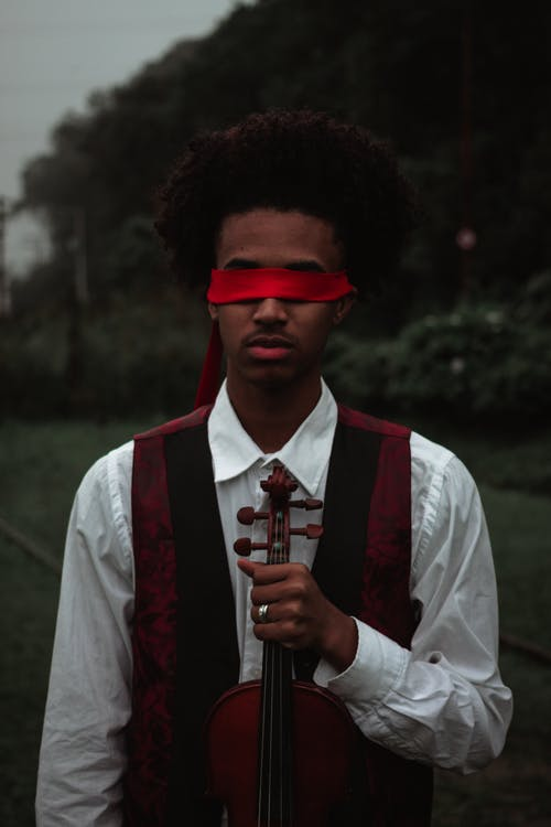 Black blindfolded serious man with violin
