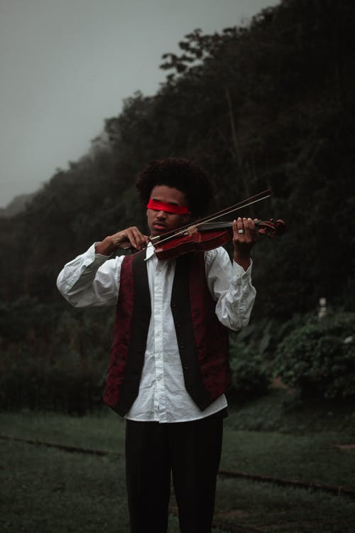 Serious young focused blindfolded talented African American male artist in elegant wear playing violin among green plants
