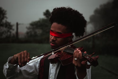 Black artist playing violin in nature