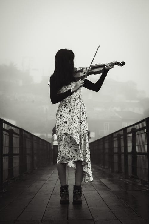 Woman playing violin on bridge in misty day