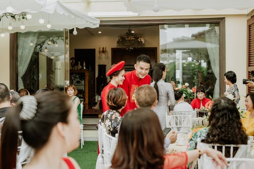 Smiling ethnic groom and bride in traditional red clothes speaking with unrecognizable guests during banquet