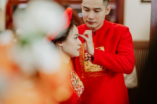 Crop Asian groom touching face of stylish bride