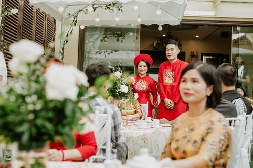 Asian newlywed couple near table with guests on wedding day