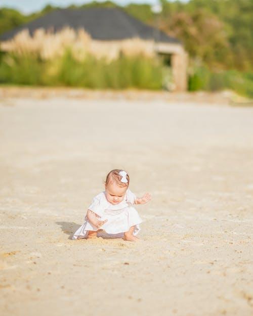 Full body adorable little girl in white dress sitting on haunches on sandy terrain against rural house on sunny summer weather