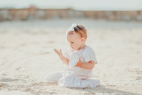 Full body cute content little girl in stylish summer dress sitting on shore and playing with warm sand on sunny day