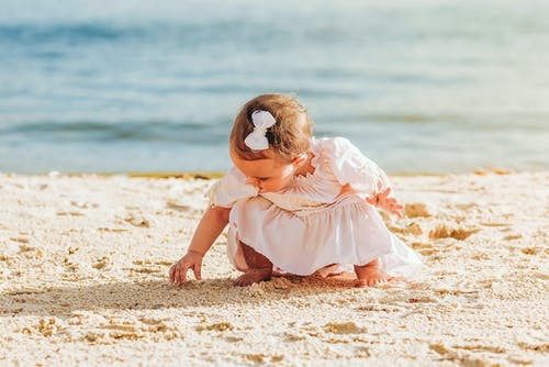 Little girl playing with sand on seashore