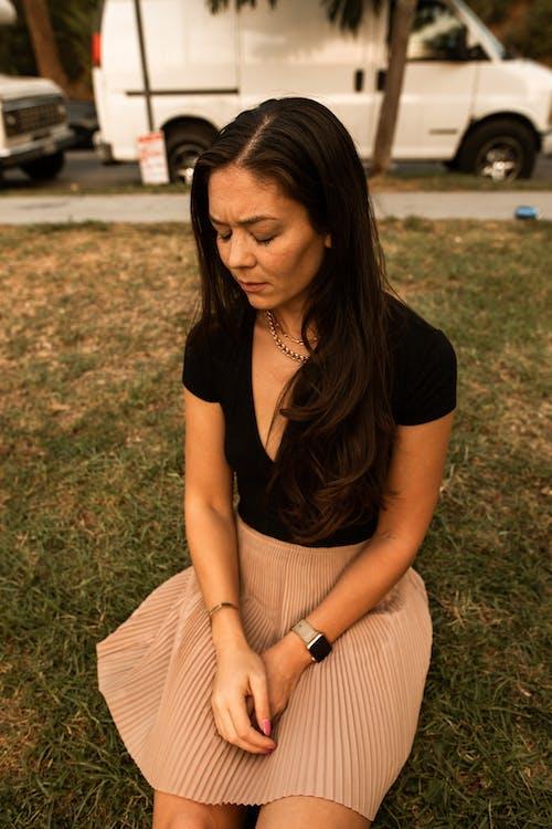 Woman in Black Shirt Sitting on Green Grass Field