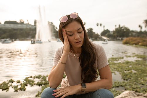 Woman in Brown T-shirt and Blue Denim Jeans Sitting on Gray Rock Near Body of With With With With