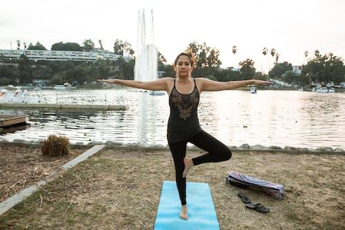 Woman in Black Tank Top and Black Leggings Doing Yoga Near Lake