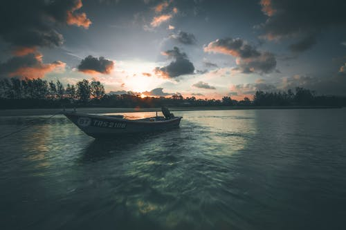 Boat floating in rippling water of river
