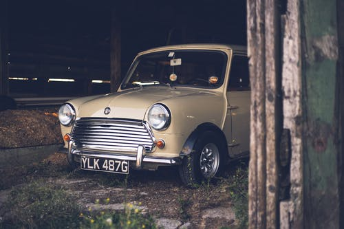 Stylish retro car placed on ground in old wooden barn in courtyard in daytime