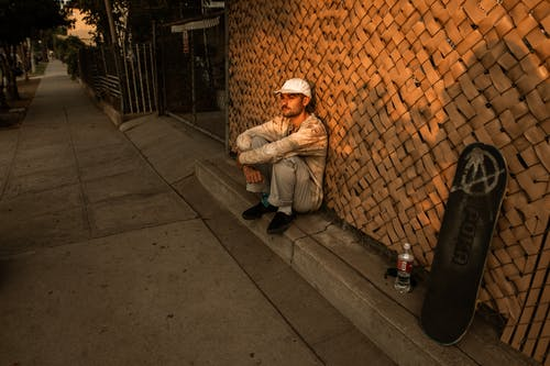 Man Sitting on Sidewalk