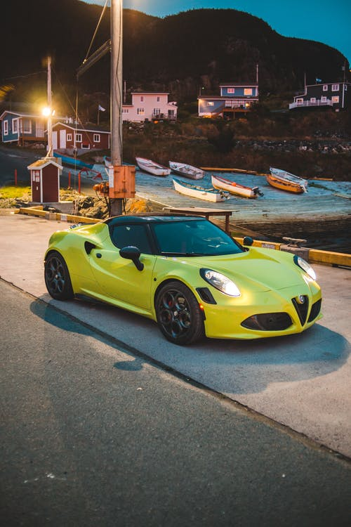 Expensive sport automobile with headlights on parked along roadway under street lights in countryside surrounded by mountains and beach at night
