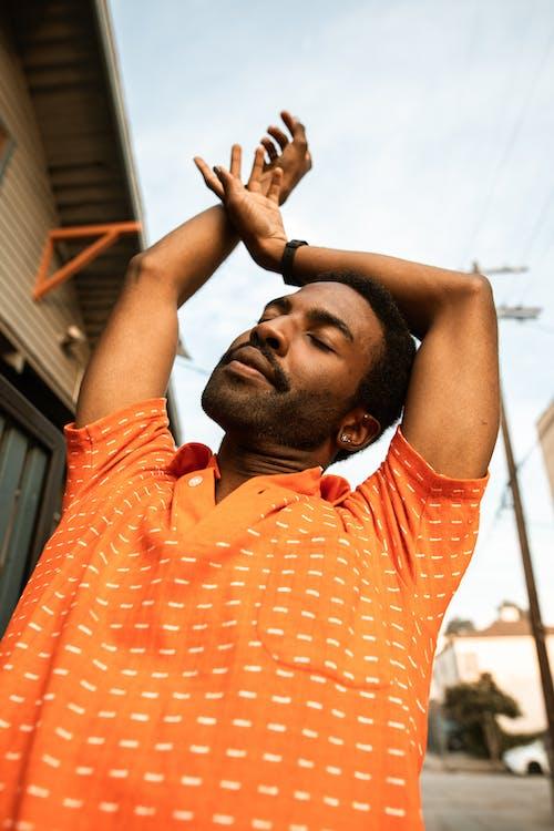 Man in Orange and White Stripe Polo Shirt Raising His Hands