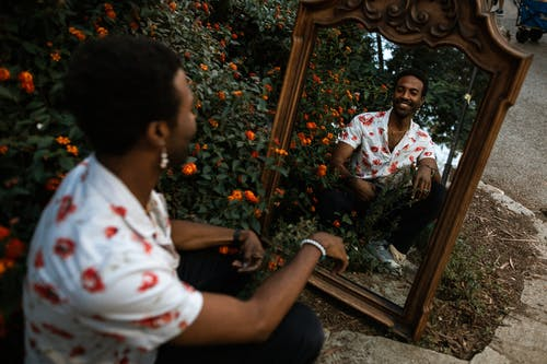 Smiling Man Looking at Himself in a Mirror