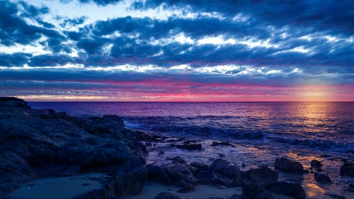 Rocky Shore Under Blue and White Cloudy Sky