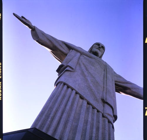 Picture of huge statue of Jesus Christ with arms spread under blue sky in Rio de Janeiro