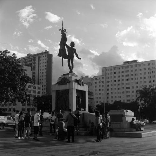 Black and white tourists exploring monument with male statue in modern city district