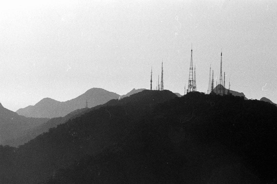 Monochrome vintage photo of tall power line tower on top of black mountain ridge
