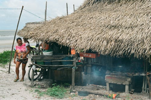 Ethnic woman walking at small hut with thatched roof in local poor village on ocean shore