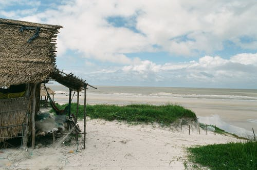 Poor indigenous cabin with thatched roof on sandy coastline with wavy ocean in cloudy day