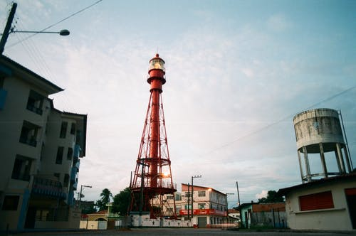 From below of red metal tower of lighthouse in urban dock with industrial buildings around