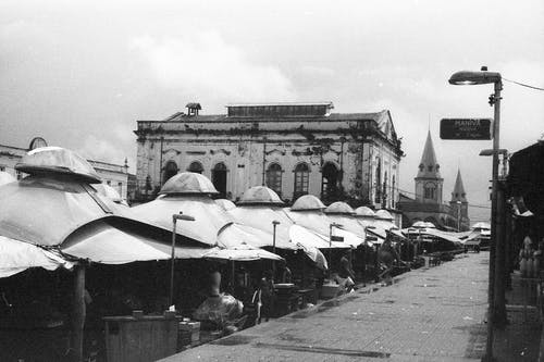 Black and white city market street with empty stalls against old weathered building